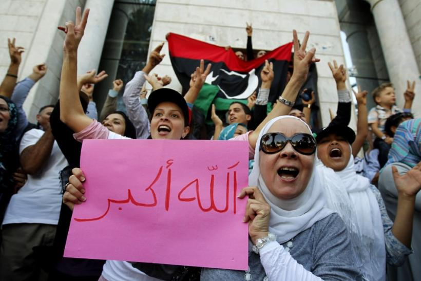 Libyan refugees in Tunisia celebrate after hearing news that Libyan leader Muammar Gaddafi was killed in Sirte, outside their embassy in Tunis