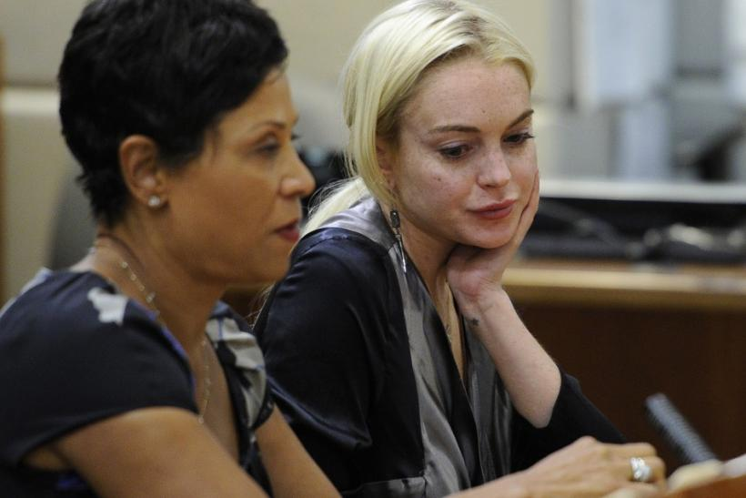Actress Lindsay Lohan sits in court with her lawyer Shawn Chapman Holley, during a compliance check to report her progress on 480 hours of community service she must do for shoplifting a necklace from a Venice jeweler, in Los Angeles