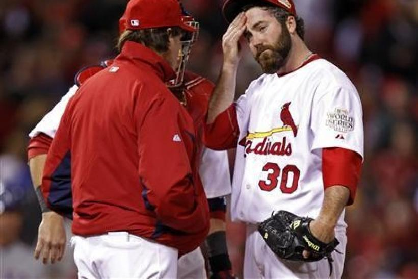 St. Louis Cardinals relief pitcher Jason Motte (R) reacts as manager Tony La Russa takes him from the game in the ninth inning of play against the Texas Rangers in Game 2 of MLB's World Series baseball championship in St. Louis, Missouri