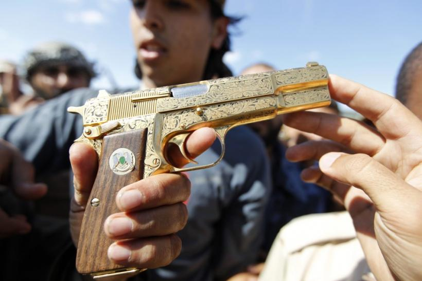 An anti-Gaddafi fighter shows the media what they say was the golden pistol of Muammar Gaddafi, near Sirte