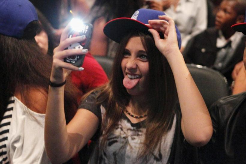 Paris Michael Katherine Jackson, the daughter of late singer Michael Jackson, sticks out her tongue as she takes a photo with a mobile phone before R&B artist Chris Brown performs in concert during the F.A.M.E. Tour in Los Angeles