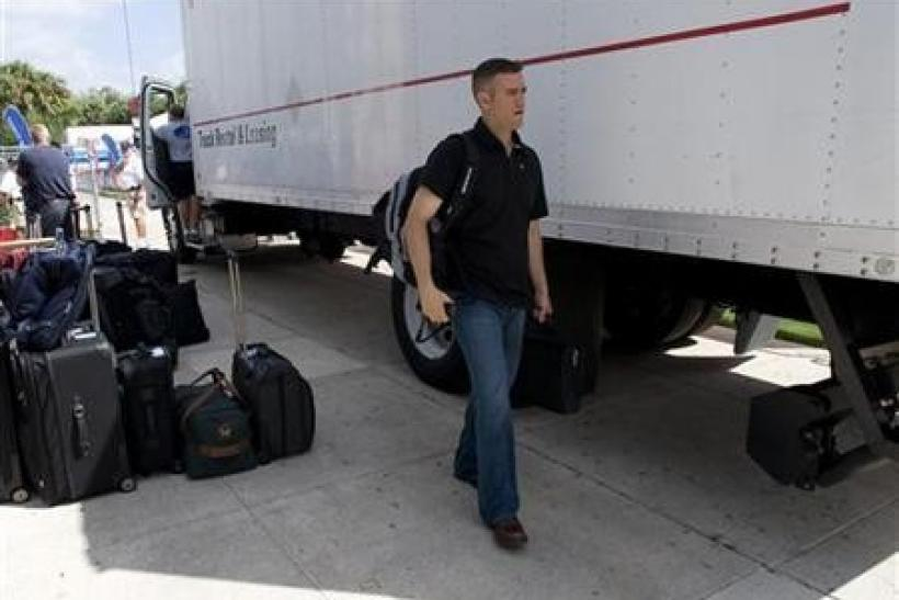 Theo Epstein walks by a van loaded with luggage in Fort Myers, Florida