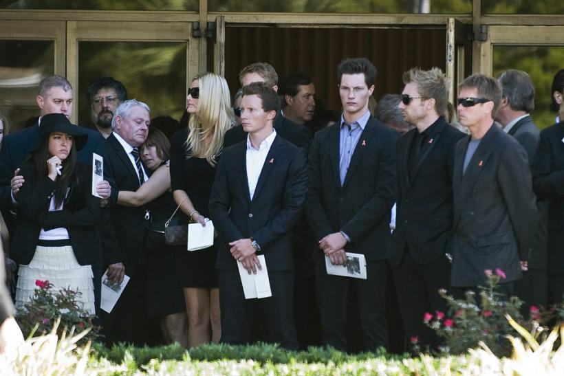 Friends of IndyCar driver Dan Wheldon look on as his casket is loaded into a hearse outside the First Presbyterian Church of St. Petersburg during a funeral service in St. Petersburg
