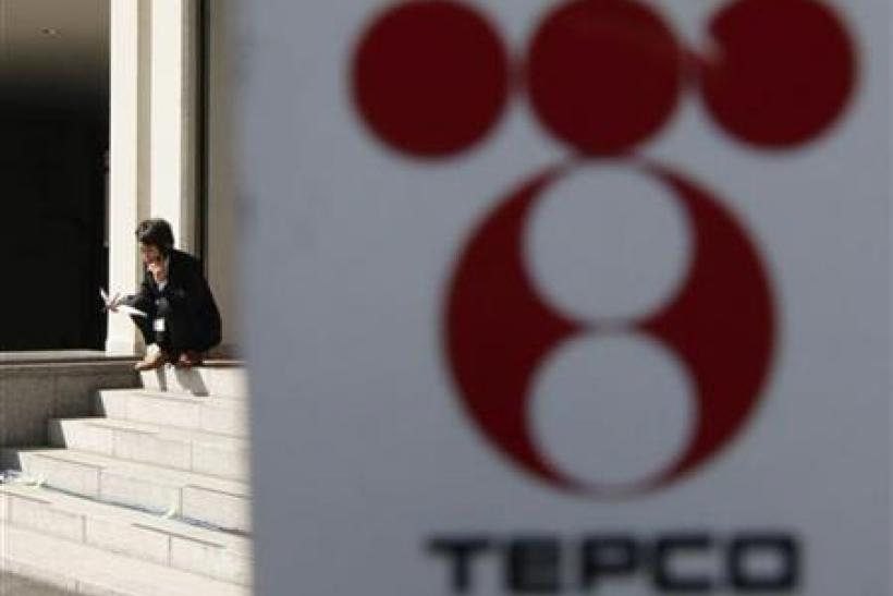 A man is seen behind the logo of TEPCO at the company's headquarters in Tokyo