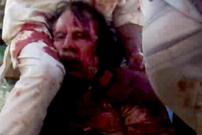 Frame grab of former Libyan leader Moammar Gadhafi, covered in blood, being held on the ground by NTC fighters in Sirte