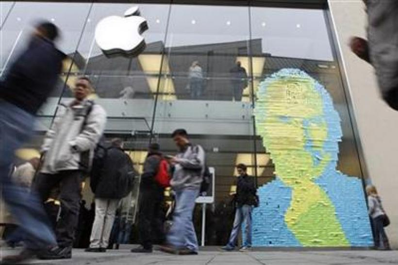 Adhesive notes show face of Apple co-founder and former CEO Jobs on window of apple store in Munich