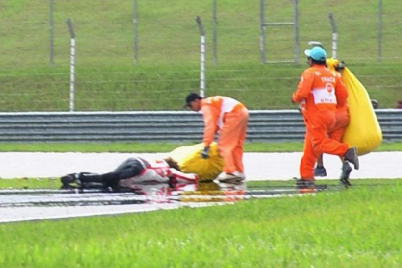 Honda MotoGP's Marco Simoncelli of Italy lies on the ground