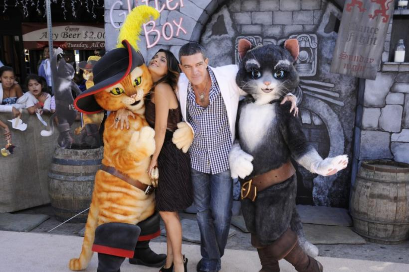 """Cast members Antonio Banderas (R) and Salma Hayek (L) pose with characters at the premiere of the animated film """"Puss In Boots"""" in Los Angeles"""