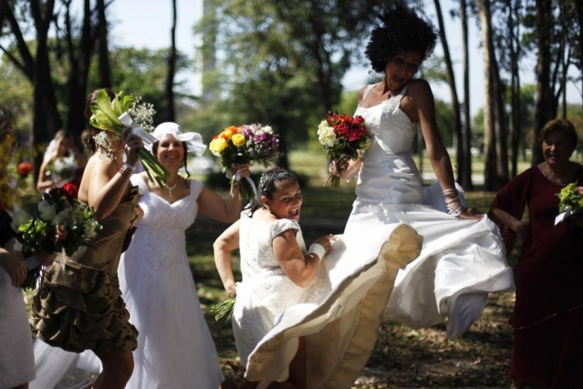 """Women in wedding gowns jump during the """"Parade of Brides"""" in Sao Paulo"""