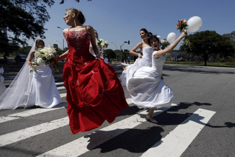 """Women in wedding gowns jump on the street during a """"Parade of Brides"""" in Sao Paulo"""