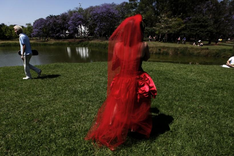 """A woman in a red wedding gown uses her mobile phone during the """"Parade of Brides"""" at Ibirapuera park in Sao Paulo"""