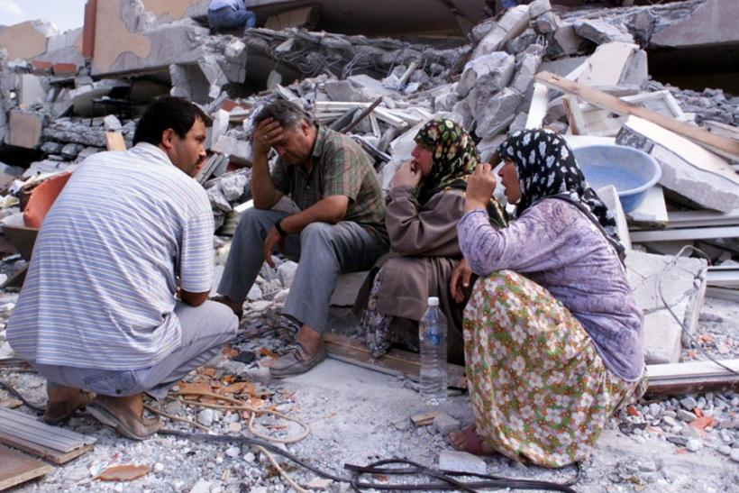 Residents sit in front of their destroyed apartment blocks in Izmit, Turkey.