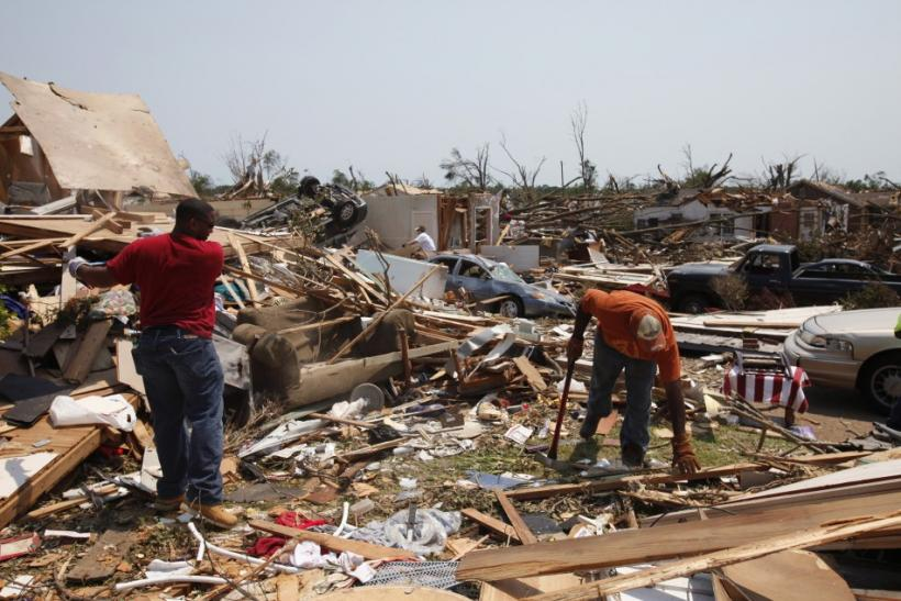 Men move debris in yard of friend the aftermath of deadly tornados in badly-damaged Alberta neighborhood of Tuscaloosa