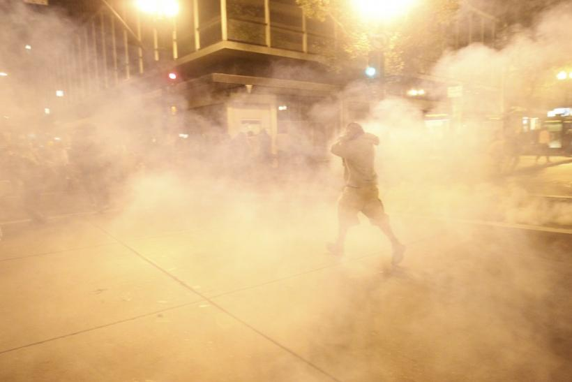 A masked Occupy Wall St. demonstrator walks away as authorities deploy tear gas during an demonstration in response to an early morning police raid which displaced Occupy Oakland's tent city in Oakland