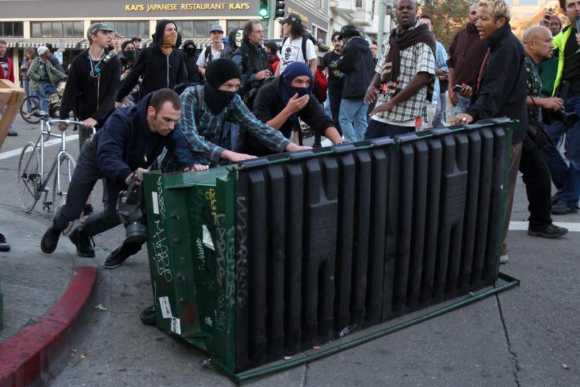 """A group of """"Occupy Wall Street"""" demonstrators pushes a garbage container toward a line of police officers during a demonstration in Oakland"""