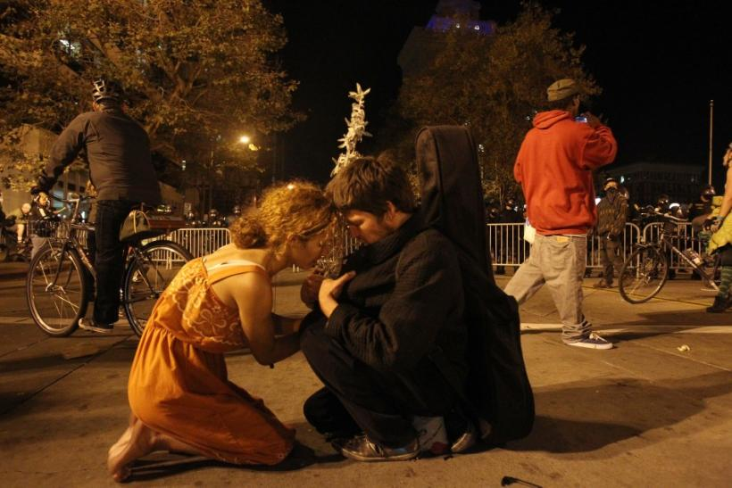 """""""Occupy Wall Street"""" demonstrators kneel on the ground during a demonstration in Oakland"""