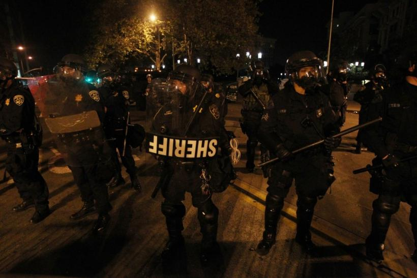 """A group of police officers stand ready near Oakland City Hall, as """"Occupy Wall Street"""" demonstrators rally"""