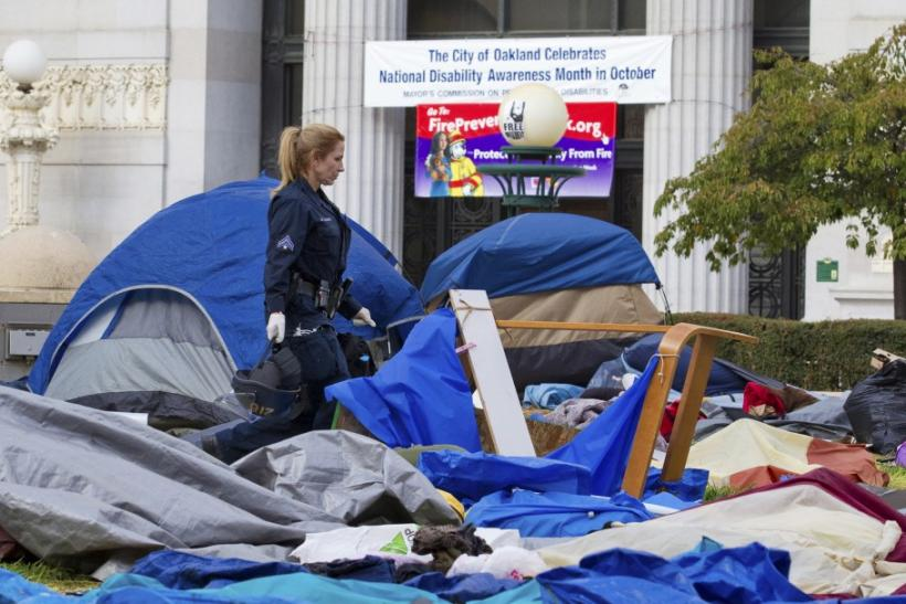 A police officer walks through a closed-down camp of anti-Wall Street protesters in Oakland