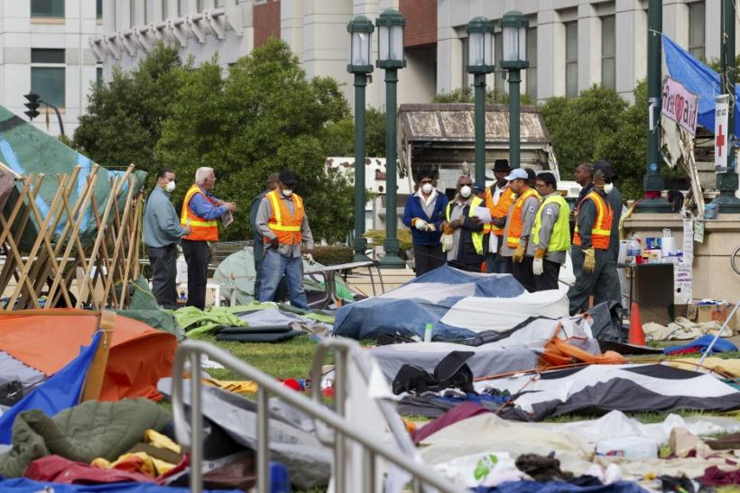 Workers prepare to clean up debris scattered throughout a closed-down camp of anti-Wall Street protesters in Oakland