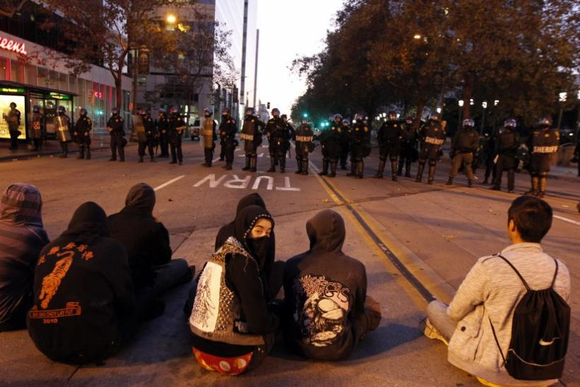 People sit in the street in front of a police line at City Hall during an anti-Wall Street protest in Oakland