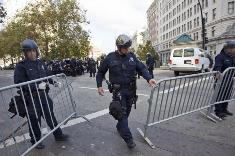 Policemen place barricades around a closed-down camp of anti-Wall Street protesters in Oakland