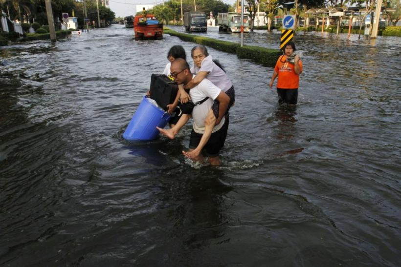 A man carries his mother during an evacuation as floods advance into Bangkok