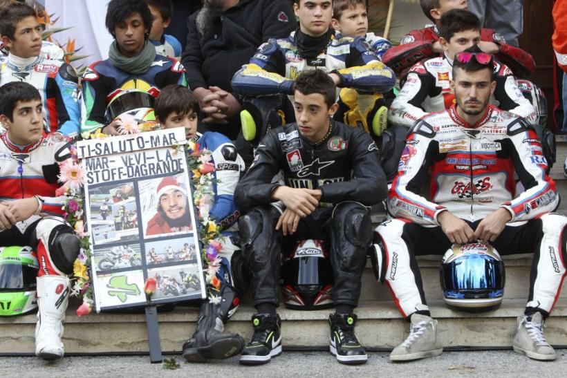 Young riders wait for the coffin of Honda MotoGP rider Marco Simoncelli to arrive for his funeral service in Coriano
