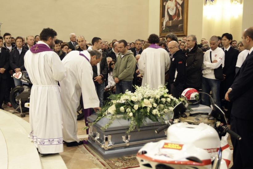 A priest blesses the coffin of Honda MotoGP rider Marco Simoncelli during his funeral service at a church in Coriano