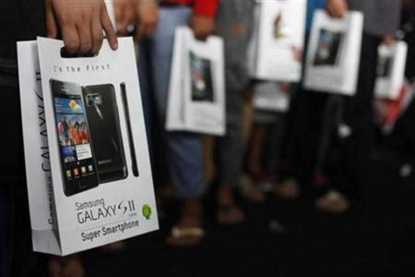 Customers hold their newly purchased Samsung Galaxy S2 android phone in Jakarta