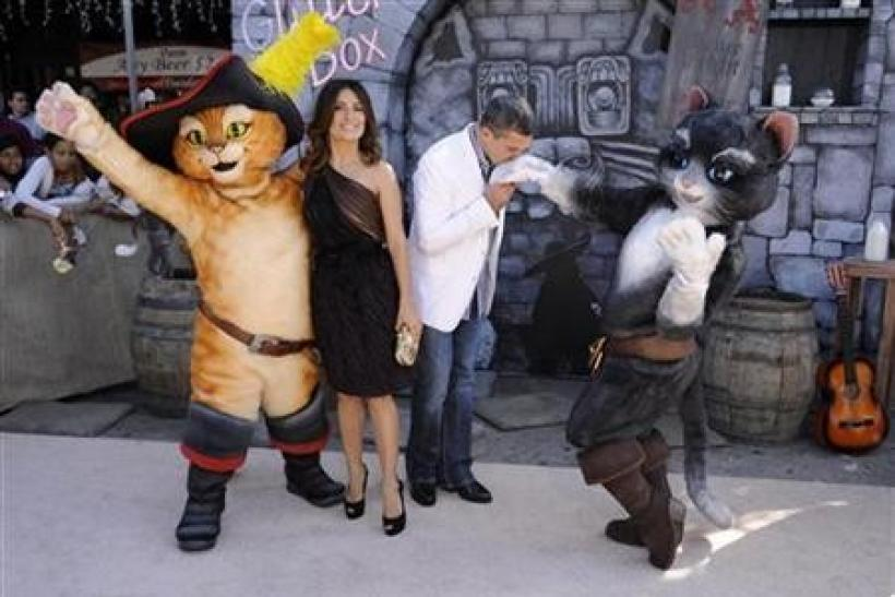 Cast members Antonio Banderas (R) and Salma Hayek pose with characters at the premiere of the animated film ''Puss In Boots'' in Los Angeles