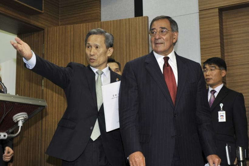 South Korean Defense Minister Kim ushers U.S. Defense Secretary Panetta towards a joint news conference in Seoul