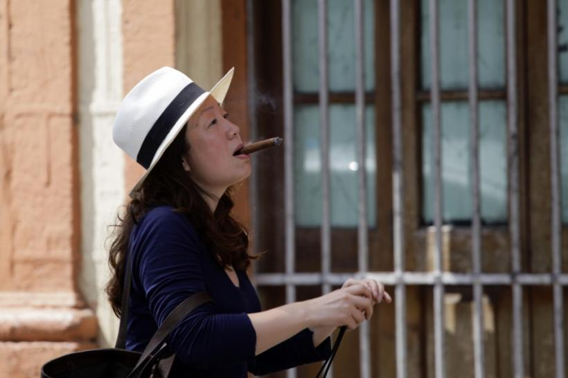 A woman smoking a cigar arrives at the Partagas factory in Havana for a visit during the ongoing annual Cuban cigar festival