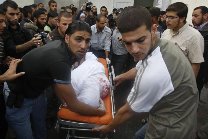 Palestinians wheel the body of a militant killed in an Israeli air strike at a hospital in the Gaza Strip