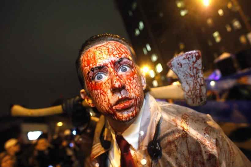 A man covered in fake blood carries an axe as he participates in the annuall Halloween parade in Greenwich Village in New York
