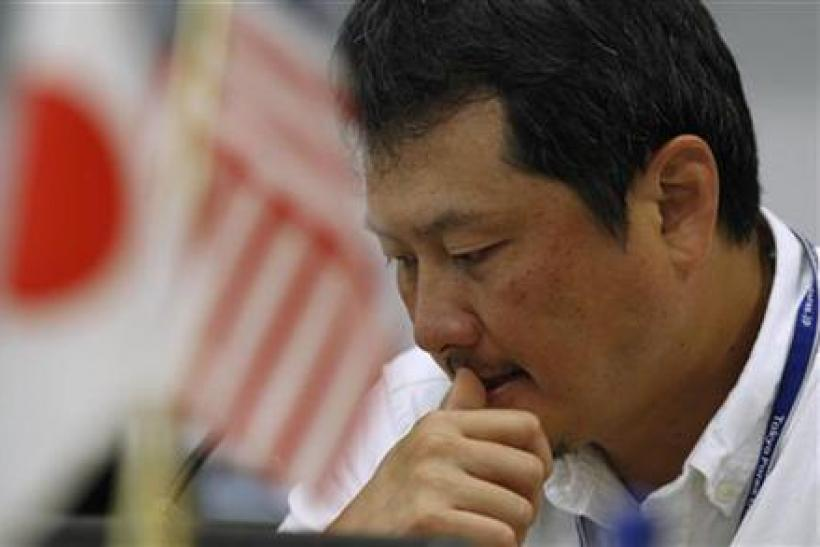 A foreign exchange broker rests his thumb on his lips as he is pictured near Japanese and American flags at a trading room in Tokyo