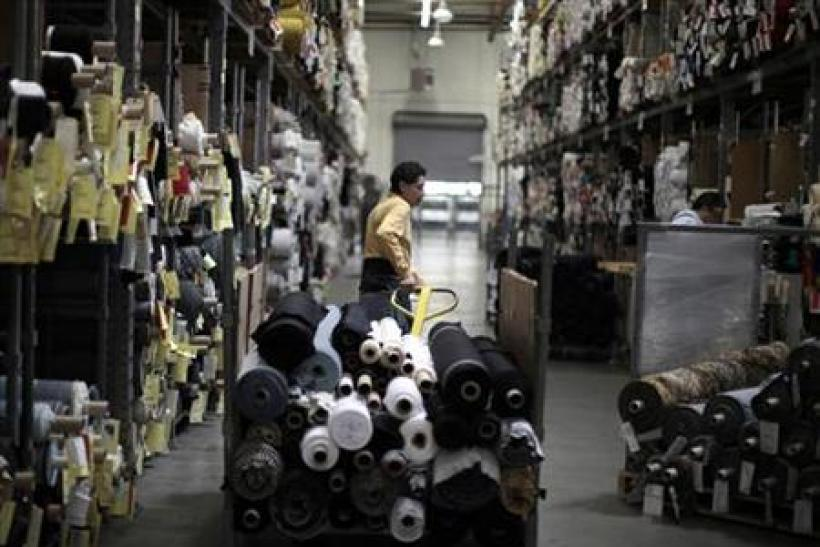 A worker wheels rolls of cloth through the Karen Kane clothing company in Los Angeles