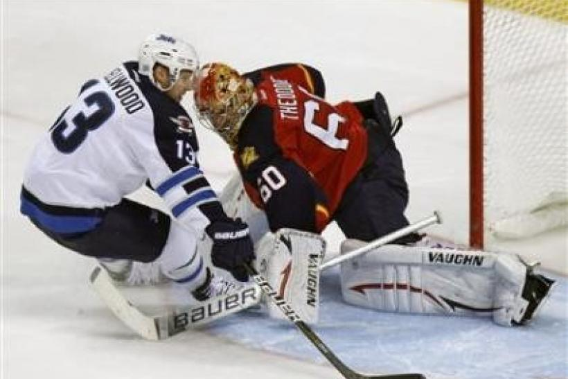 Winnipeg Jets Kyle Wellwood (L), scores on Florida Panthers goaltender Jose Theodore in a shootout during NHL hockey game in Sunrise, Florida