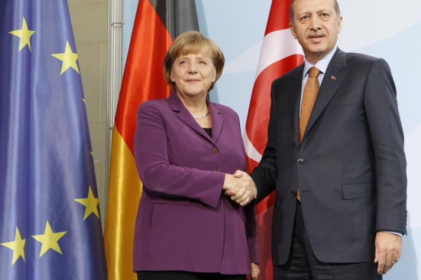German Chancellor Angela Merkel and Turkish Prime Minister Tayyip Erdogan shake hands as they speak to media after meeting in the Chancellery in Berlin