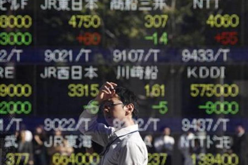 A man is reflected on an electronic board displaying stock prices outside a brokerage in Tokyo