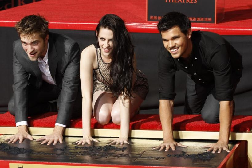 Actors Robert Pattinson (left), Kristen Stewart and Taylor Lautner put their handprints in cement during a hand and footprint ceremony at the Grauman's Chinese Theatre in Hollywood, California on November 3, 2011.