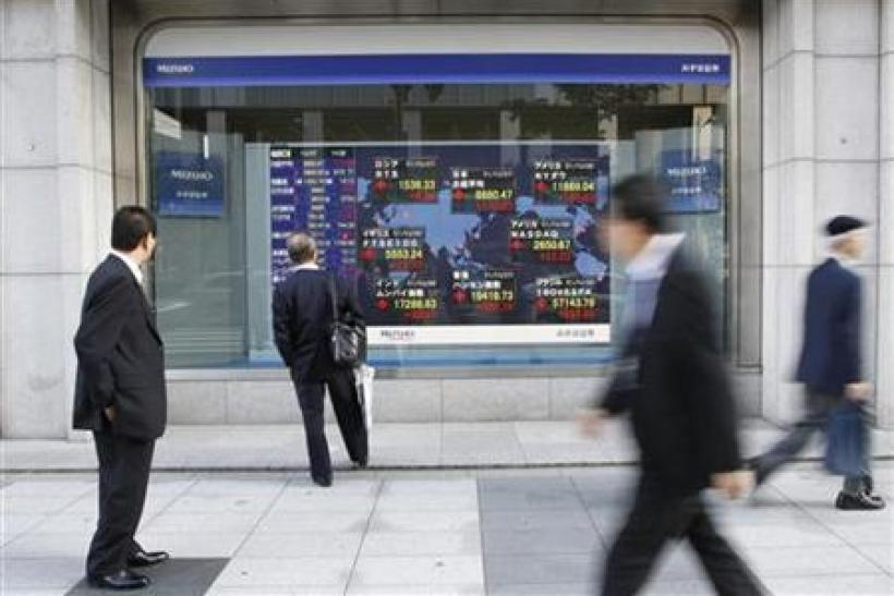 Passersby look at an electronic board displaying a rise in major market indices around the world, outside a brokerage in Tokyo