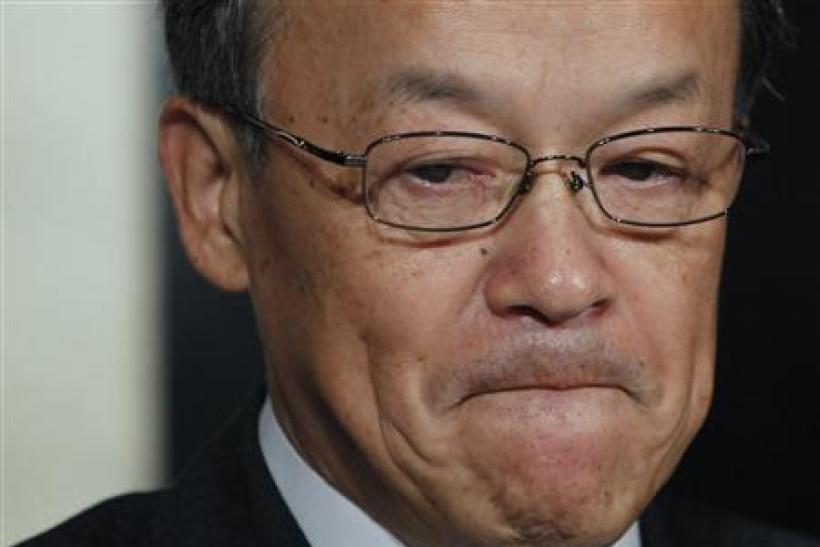 Olympus Corp's President Shuichi Takayama reacts at a news conference in Tokyo