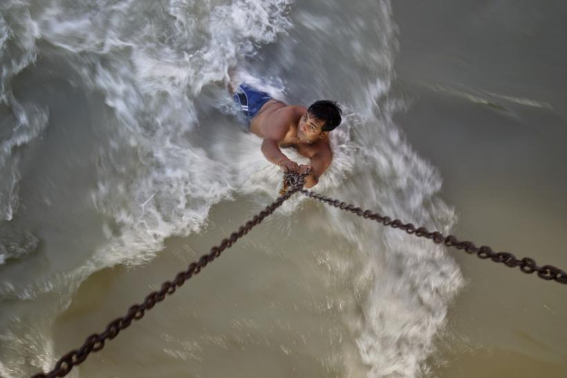 A man clings to chains suspended from a bridge as he bathes in rapidly flowing waters of the Ganges river in Haridwar
