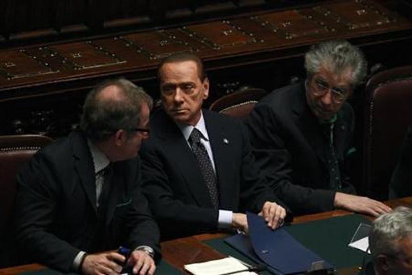 Italian PM Berlusconi holds and saves a memo during a finances vote at the parliament in Rome