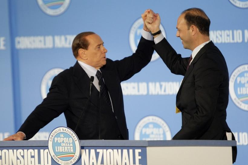 Italy's PM Berlusconi holds the hand of the former justice minister Alfano after Alfano was elected as new party's national political secretary during the PDL party national congress in Rome