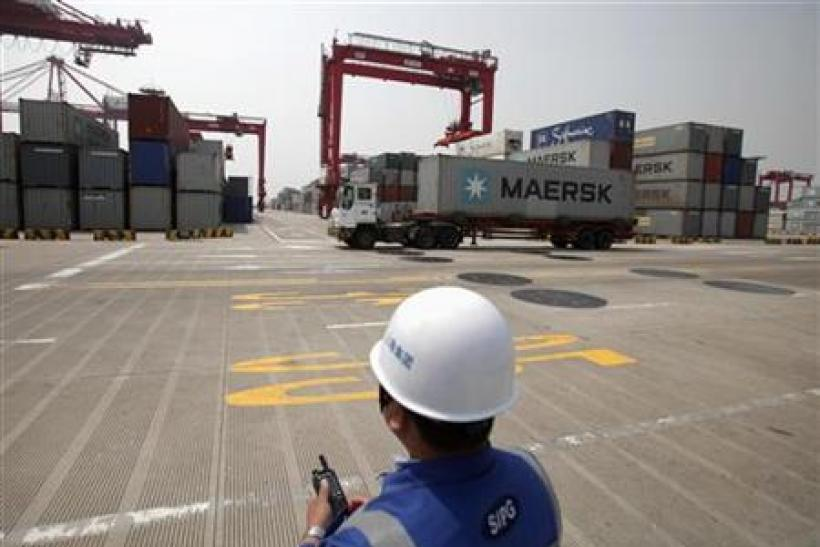 A port worker holds a radio as he works at a container area at the Yangshan Deep Water Port, south of Shanghai