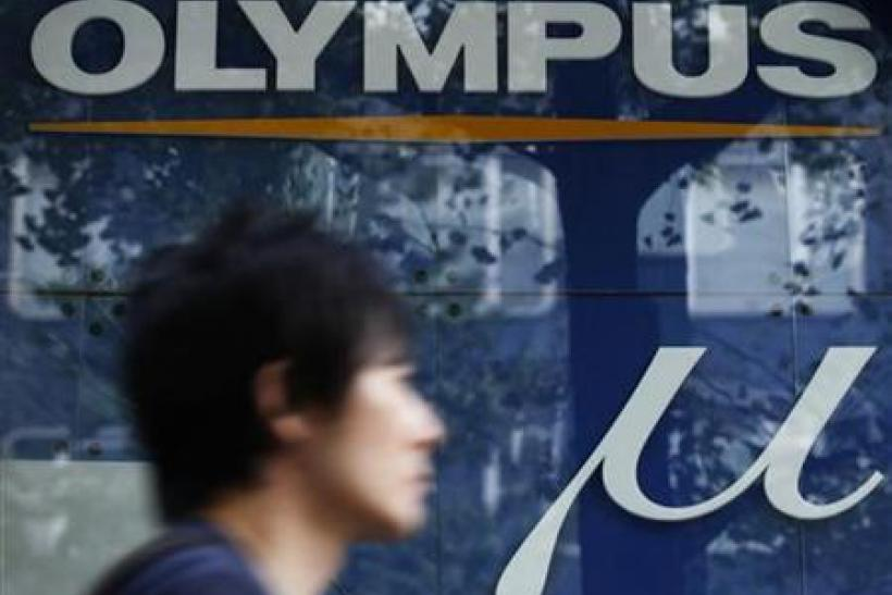 A man walks past an advertisement of Japan's Olympus Corp in Tokyo
