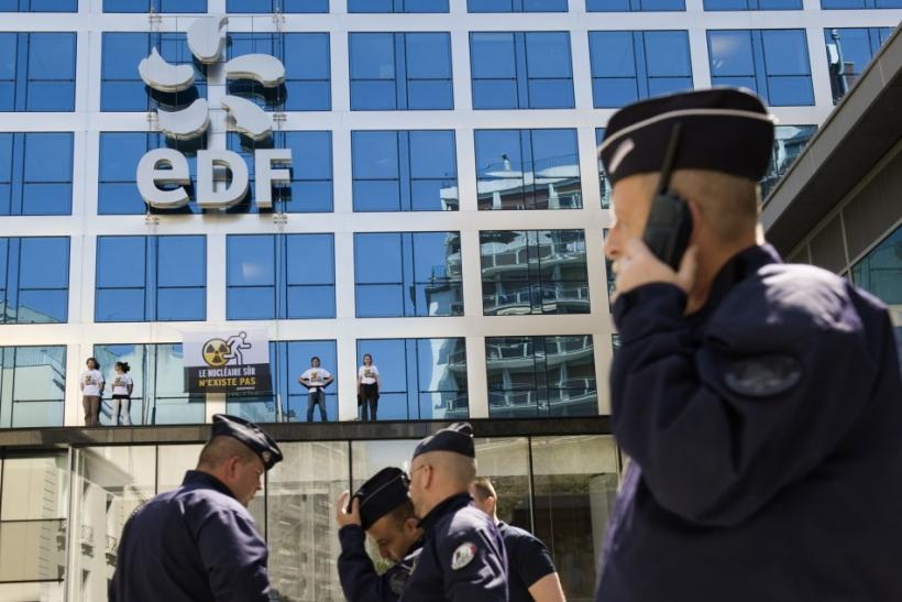 French police take position outside EDF headquarters as Greenpeace members stand on a building ledge with a protest banner in Paris