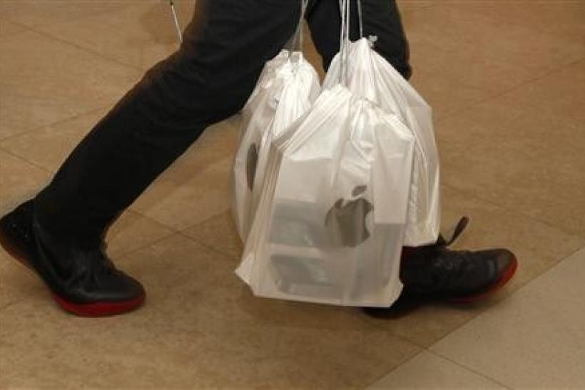 A man carries packs of Apple iPhone 4S, with each pack containing five sets, outside an Apple store in Hong Kong November 11, 2011. Many of Apple's latest smartphones are expected to ship into mainland China for higher resale prices.
