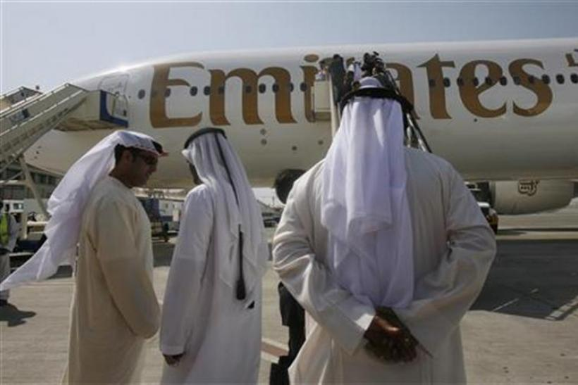Local people stand near an Emirates airplane at Dubai airport